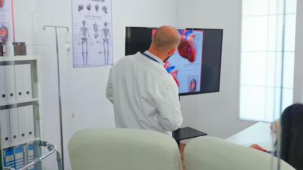 Doświadczony lekarz mężczyzna omawiający problemy z sercem za pomocą cyfrowego obrazu, wraz z kwalifikowanymi kolegami w sali konferencyjnej, wskazując na monitor. lekarze analizujący diagnozę pod kątem leczenia pacjentów