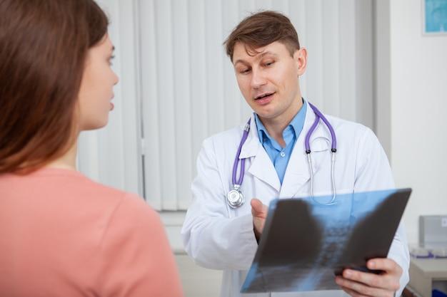 Doświadczony lekarz płci męskiej, wyjaśniający wyniki skanowania rentgenowskiego pacjentce pracującej w swoim gabinecie