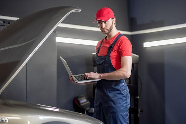 Doświadczony mechanik. młody dorosły mechanik samochodowy z decydentem myślenia laptopa w pobliżu otwartej maski samochodu w warsztacie