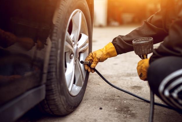 Doświadczony mechanik w pomarańczowych rękawiczkach zakłada zawór powietrza na kole samochodu, przygotowując się do zwiększenia ciśnienia.