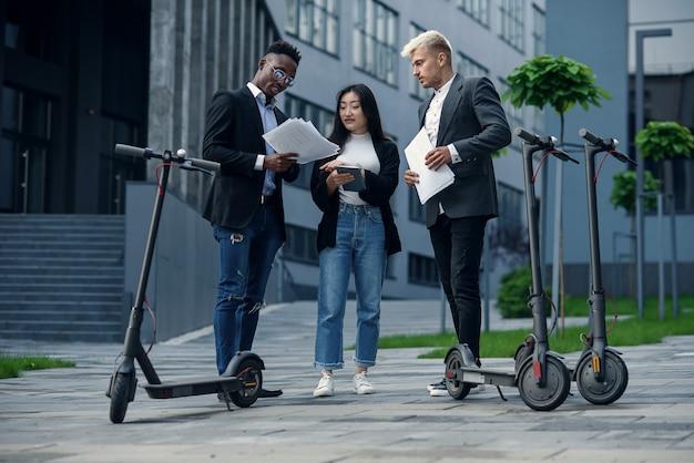 Doświadczony międzynarodowy zespół biznesowy złożony z trzech współpracowników analizuje projekt stojący w pobliżu e