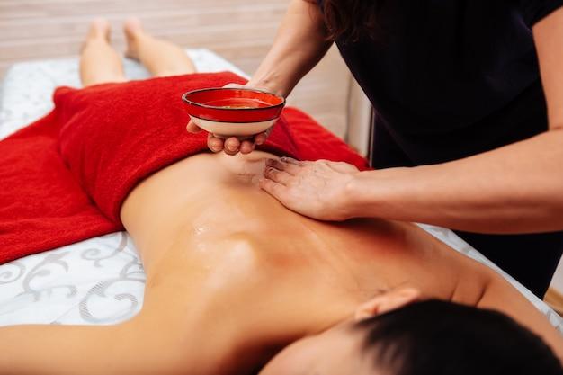 Doświadczony mistrz. skoncentrowany mistrz używający rąk do rozprowadzania zdrowego oleju na plecach zrelaksowanego klienta