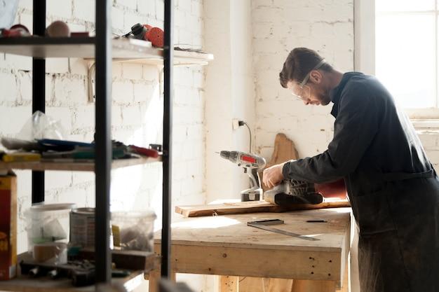 Doświadczony młody stolarz pracujący z drewnem na warsztatach stolarskich w pomieszczeniach zamkniętych