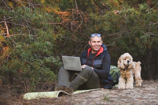 Doświadczony podróżnik korzysta z laptopa z przyjacielem zwierzakiem podczas wędrówki po lesie
