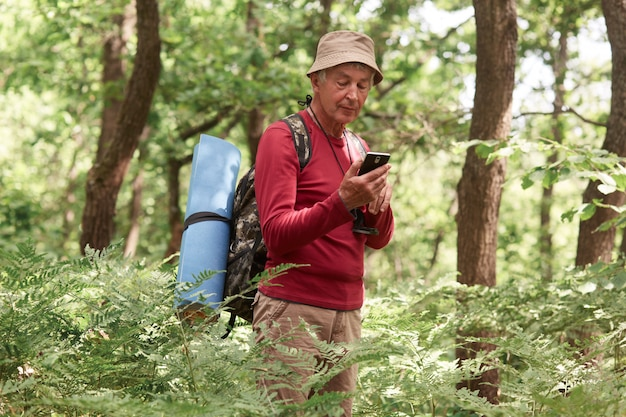 Doświadczony podróżnik trzymając smartfon w jednej ręce, używając urządzenia do orientacji, będąc samemu, mając kompas