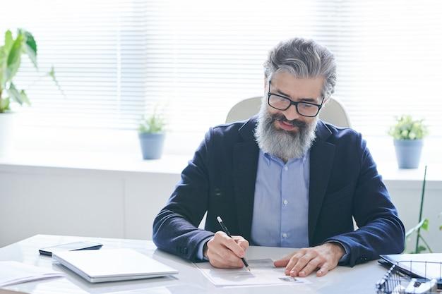 Doświadczony profesjonalista w okularach i strojach wizytowych, robiąc notatki na papierze, siedząc przy biurku przy oknie i czekając na klientów