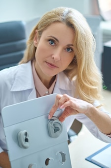 Doświadczony profesjonalny otolaryngolog demonstruje, jak nosić aparat słuchowy