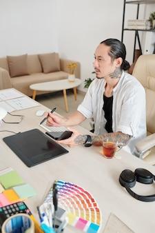 Doświadczony projektant ze smartfonem w rękach pracujący na tablecie graficznym w swoim domowym biurze