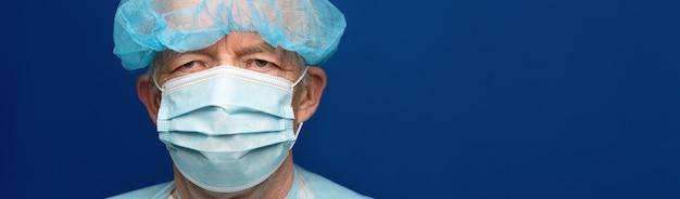 Doświadczony starszy dorosły lekarz ubrany w maskę chirurgiczną i czapkę. profilaktyczna ochrona przed chorobami zakaźnymi, koronawirusem. panoramiczny baner, kopia przestrzeń tradycyjny niebieski kolor medyczny.