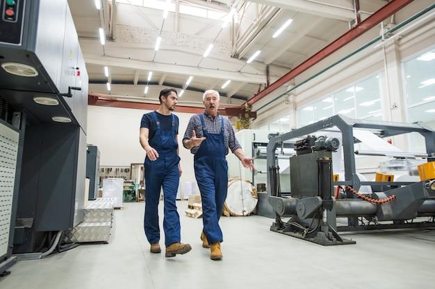 Doświadczony starszy mężczyzna w niebieskim kombinezonie gestykuluje rękami podczas interakcji z młodym pracownikiem w drukarni