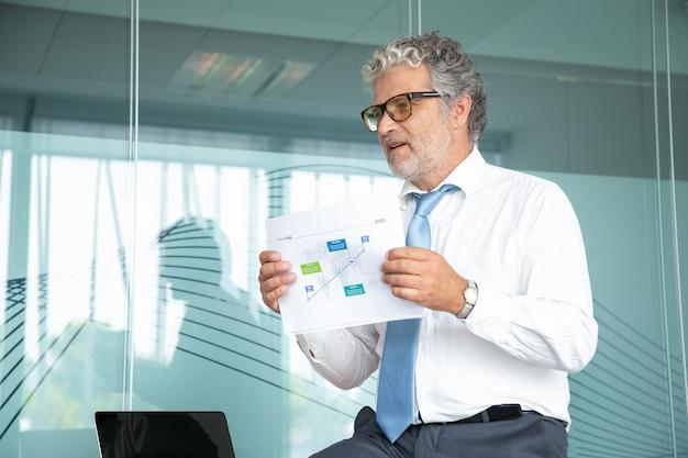 Doświadczony szef siedzi i pokazuje plan strategiczny