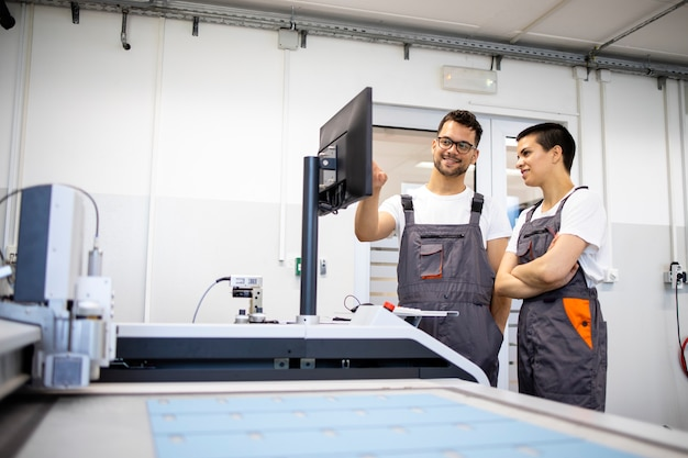 Doświadczony technik szkolący nowego pracownika do obsługi maszyny przemysłowej cnc w fabryce.