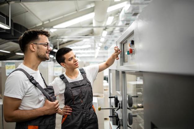 Doświadczony technik szkolący nowego pracownika do obsługi maszyny przemysłowej w fabryce.