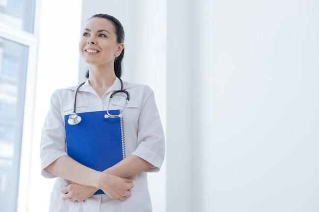 Doświadczony, troskliwy, optymistyczny lekarz pracujący w szpitalu, trzymając teczkę i uśmiechając się