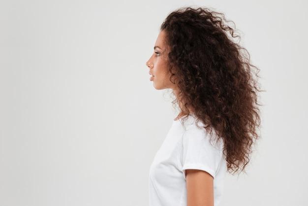 Dosyć kędzierzawa kobieta pozuje w profilu