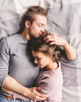 Dosyć kochająca para luxuriating w łóżku wpólnie. są przytuleni i uśmiechnięci