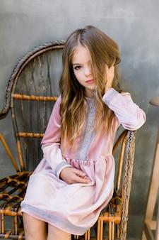 Dosyć mała dziewczyna w pięknej menchii sukni siedzi na drewnianym krześle i patrzeje marzycielskiego, piękna i mody pojęcie, salowy portret