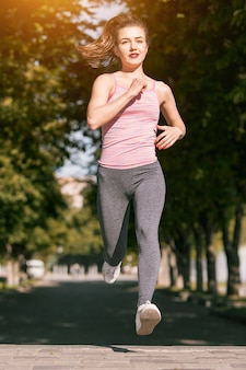 Dosyć sporty kobieta jogging przy parkiem w wschodu słońca świetle