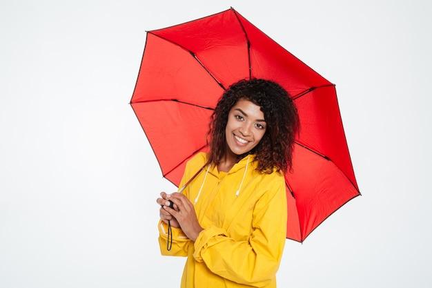 Dosyć szczęśliwa afrykańska kobieta w płaszczu pozuje z parasolem