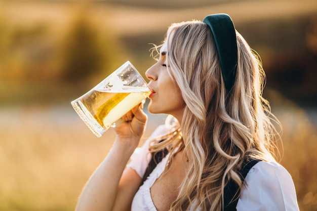 Dosyć szczęśliwa blondynka w dirndl, tradycyjna festiwalowa suknia, pije piwo outdoors w polu