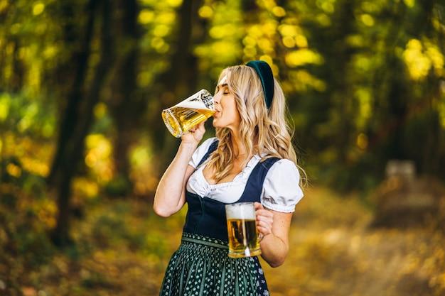 Dosyć szczęśliwa blondynka w dirndl, tradycyjnej festiwalowej sukni, pije piwo na zewnątrz w lesie