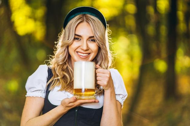 Dosyć szczęśliwa blondynka w dirndl, tradycyjnej festiwalowej sukni, trzyma kubek piwa na zewnątrz w lesie