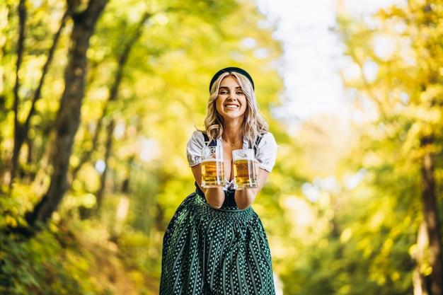 Dosyć szczęśliwa blondynka w dirndl, tradycyjnej festiwalowej sukni, trzymająca dwa kufle piwa na zewnątrz w lesie