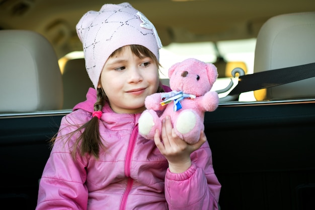 Dosyć szczęśliwa dziecko dziewczyna bawić się z różowym zabawkarskim misiem siedzi w bagażniku samochodu.