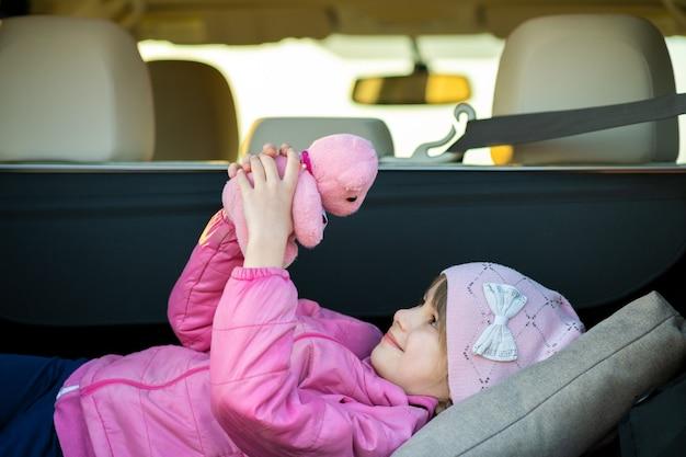 Dosyć szczęśliwa dziecko dziewczyna bawić się z różowym zabawkarskim misiem w bagażniku samochodu.
