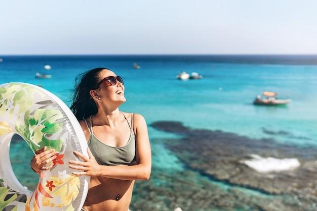 Dosyć szczęśliwej niecki azjatykcia dziewczyna z dużym pławikiem behind i tłem na tle.