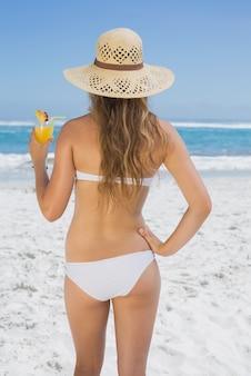 Dosyć uśmiechać się blondynki w bikini popijania koktajlu na plaży