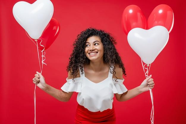 Dosyć wesoła czarna dziewczyna z kolorowych balonów helem na białym tle nad czerwonym