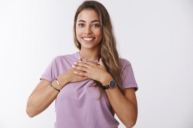 Dotknięta dziewczyna otrzymująca komplement zachwycona słuchaniem. urocza szczęśliwa przyjemna urodzinowa dziewczyna naciska dłonie na klatkę piersiową wdzięczna, wygląda na wdzięczną doceniając podnoszący na duchu prezent, uśmiechając się zadowolona