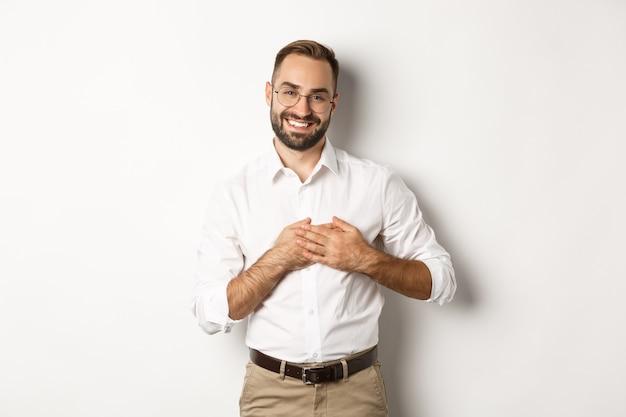 Dotknięty i wdzięczny człowiek biznesu trzymający się za ręce na sercu, uśmiechnięty wdzięczny, stojący na białym tle.