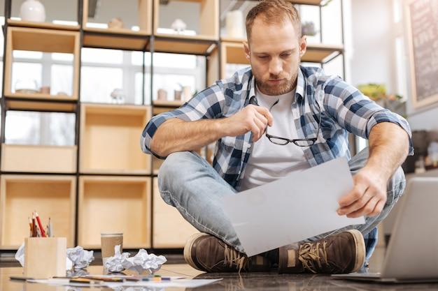Dotrzymanie terminu. zamyślony, zmęczony ciężko pracujący mężczyzna siedzący ze skrzyżowanymi nogami na podłodze i trzymając kartkę papieru podczas pracy nad projektem