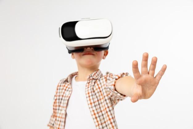 Dotykając cudu. mały chłopiec lub dziecko w dżinsach i koszuli z okularami zestaw słuchawkowy wirtualnej rzeczywistości na białym tle na tle białego studia. koncepcja najnowocześniejszych technologii, gier wideo, innowacji.