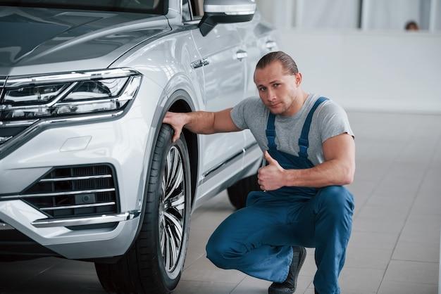 Dotykając koła. po profesjonalnej naprawie. mężczyzna patrzący na doskonale wypolerowany samochód w kolorze srebrnym.