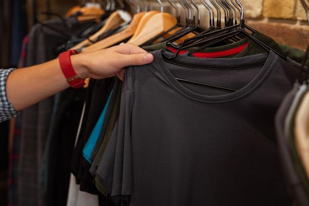 Dotykająca koszulka. ostrożny młody nabywca odwiedzający modny sklep z modną odzieżą i dotykający pięknej szarej koszulki przed zakupem