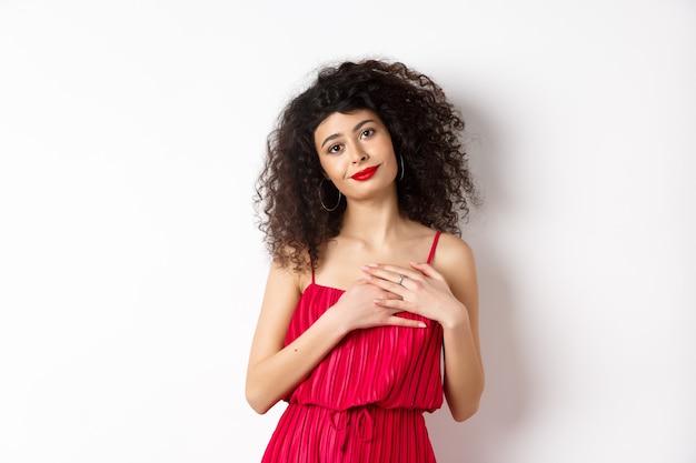 Dotykana młoda kobieta z kręconymi włosami, ubrana w czerwoną sukienkę, trzymająca ręce na sercu i uśmiechnięta wdzięczna, dziękuje, stojąc na białym tle.