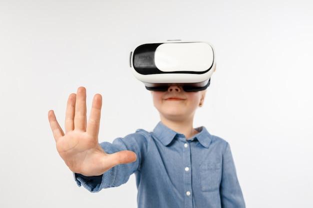 Dotykanie nieistniejące. mała dziewczynka lub dziecko w dżinsach i koszuli z okularami zestawu słuchawkowego wirtualnej rzeczywistości na białym tle na tle białego studia. koncepcja najnowocześniejszej technologii, gier wideo, innowacji.