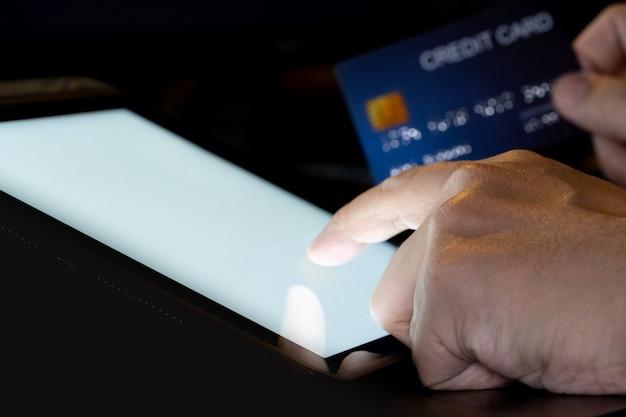 Dotykanie palcem na ekranie tabletu z oświetleniem karty kredytowej. koncepcja technologii i urządzenia telefonu komórkowego.