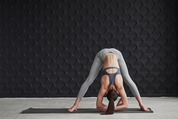 Dotykanie podłogi. dziewczyna z dobrą sylwetką fitness ma ćwiczenia w przestronnym pokoju
