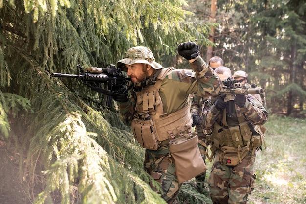 Dowódca wojskowy patrzący przez lunetę i przygotowujący swój zespół do ataku