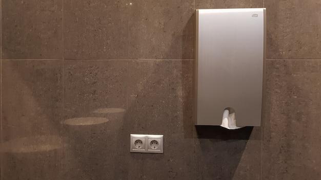 Dozownik lub uchwyt na ręczniki papierowe na szarej, wyłożonej płytkami ścianie w publicznej toalecie.