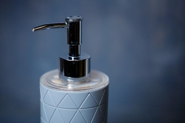 Dozownik na mydło w kolorze szarym z metalową nakrętką na szarym stole