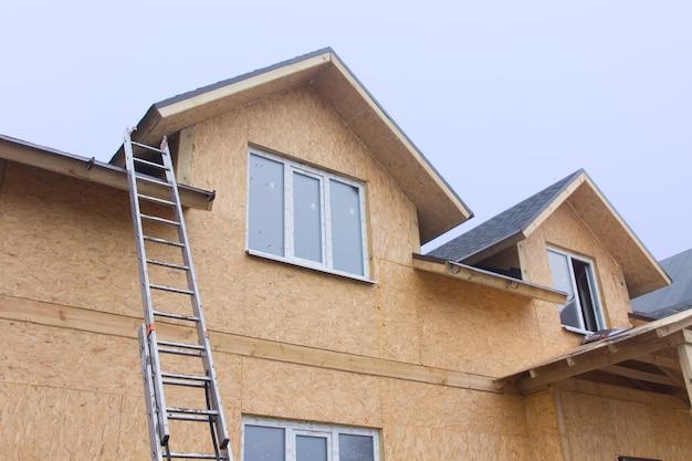 Drabina oparta o nowo wybudowany drewniany dom prowadzący na dach widziany od dołu