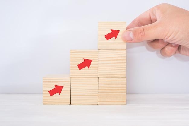 Drabina ścieżka kariery dla koncepcji procesu sukcesu rozwoju biznesu. układanie rąk do układania bloków drewnianych jako schody schodowe ze strzałką w górę
