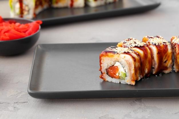 Dragon roll sushi z węgorzem na czarnej płycie ceramicznej z bliska