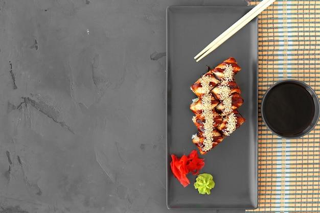 Dragon roll sushi z węgorzem na szarym tle widok z góry