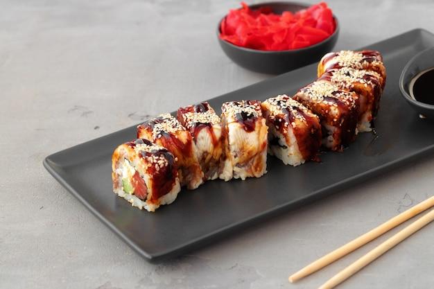 Dragon sushi roll z węgorzem na czarnym talerzu ceramicznym